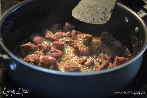 Ягнятину кубиками для тушения посолить и поперчить. Разогреть сковороду с маслом, выложить кусочками мясо и обжаривать примерно 2 минуты каждая сторона. Переложить на тарелку, оставить 1 ст.л. жира, остальной жир слить.