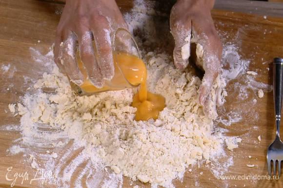 Муку с маслом собрать в холмик, сделать в центре углубление и в несколько приемов влить в него яичную массу, каждый раз перемешивая, затем руками вымесить тесто.