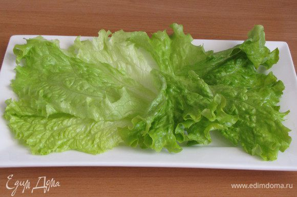 На блюдо или порционную тарелку выложить промытые салатные листья.