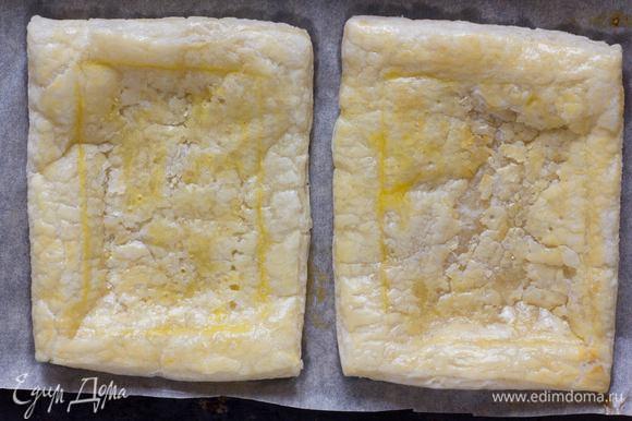 Противень выстелить бумагой для выпечки, выложить тесто, сделать легкий надрез в виде квадрата, смазать поверхность желтком и выпекать в духовке 8–10 минут, до золотистого цвета.