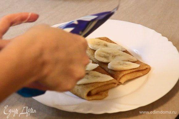 Сверху блинчика выкладываем нарезанные бананы и поливаем сгущённым молоком.