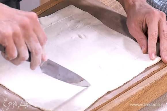 Отступая на полтора сантиметра от краев и не прорезая тесто насквозь, ножом прочертить прямоугольник меньшей площади, так чтобы получились бортики.