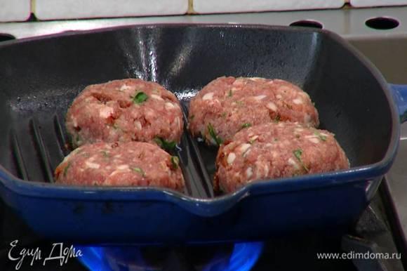 Разогреть в сковороде-гриль оливковое масло и пожарить котлеты с двух сторон до готовности.