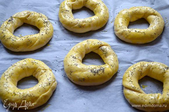 Выложить их на на противень и оставить для расстойки ещё на 20 минут. Затем смазать яйцом и по желанию присыпать маком.