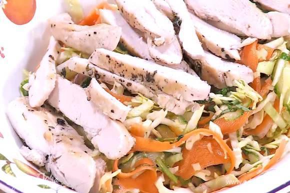 Выложить салат на тарелку, сверху разложить куриное мясо.