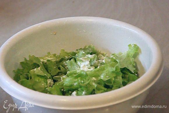 В листья салата добавляем сметану и перемешиваем.