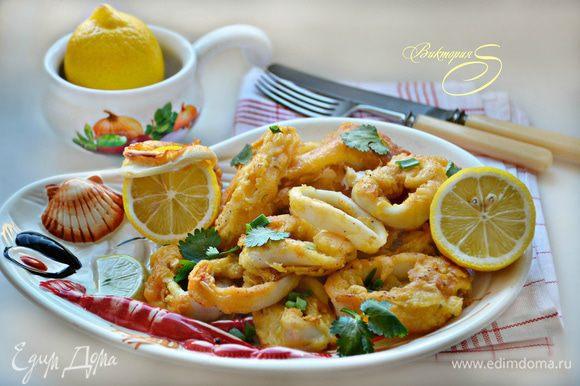 Подавайте кальмары с лимоном, посыпав зеленью. Приятного вам аппетита!