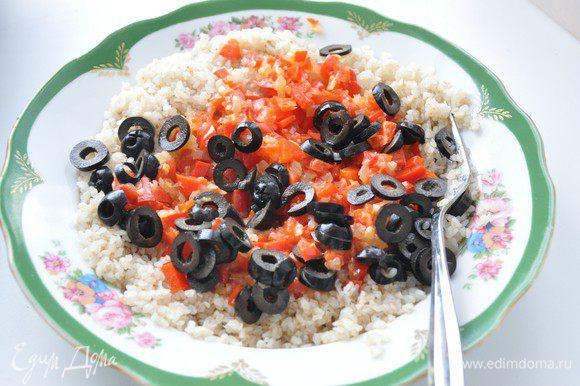 Включить разогреваться духовку до 180°С. Маслины нарезать кружочками. Выложить приготовленные овощи к крупке, посолить и поперчить по вкусу, перемешать.