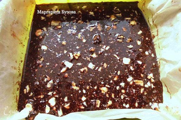 Вылить шоколад в форму и аккуратно распределить его. У меня силиконовая форма размером 20х20 см. Предварительно нужно выстелить ее бумагой для выпечки. Присыпать шоколад оставшимися орехами и дать ему застыть. Готовый десерт поломать на кусочки и подавать.