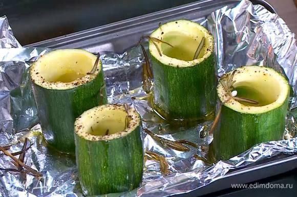 Форму выстелить пищевой фольгой, поместить на нее цукини выемками вверх, посолить, поперчить, сбрызнуть оливковым маслом, посыпать листьями розмарина и запекать под хорошо разогретым грилем 5‒7 минут.