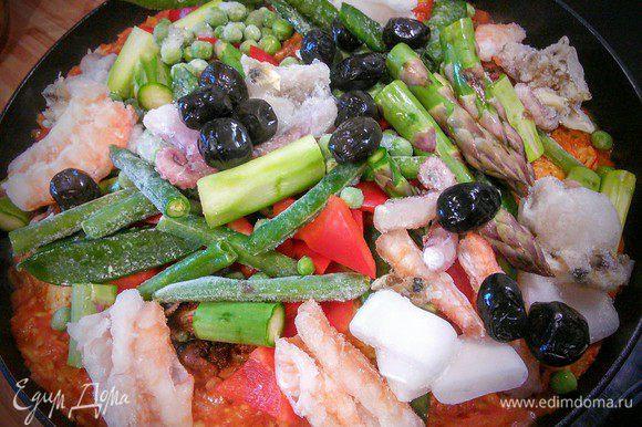 Через примерно 10 мин добавляем овощи, маслины и морепродукты (у меня тоже замороженные). Солим и перчим. Перемешиваем. Тушим под крышкой еще 10-15 минут, до готовности риса и мяса.