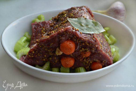 Посолите говядину и натрите перцем и горчицей. Затем с помощью ножа сделайте надрезы и нашпигуйте мясо дольками чеснока и морковью. Уложите мясо в форму, смазанную растительным маслом. Вокруг уложите нарезанные кусочки сельдерея, лавровый лист. Накройте кусок мяса фольгой и запекайте в разогретой до 170°С духовке около 1,5 часов, периодически поливая мясо выделившимся соком.