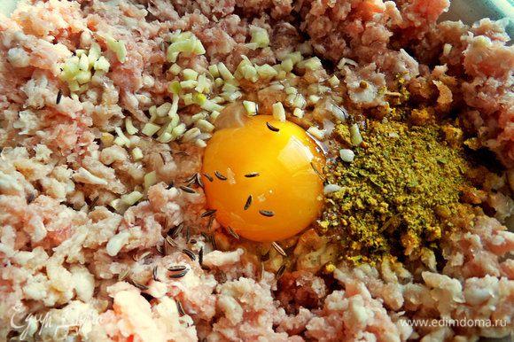 В фарш вбить яйцо, выдавить или порубить чеснок, всыпать тмин и смесь приправ (горчица, чили, базилик, морковь, лук, куркума).