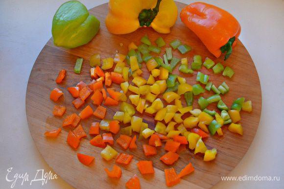 Половинки разноцветного болгарского перца помыть, освободить от семян и перегородок, нарезать небольшими кубиками. Разогреть в сковороде растительное масло, слегка обжарить чеснок и затем вынуть. В полученном чесночном масле обжарить перец в течение 3-5 минут.