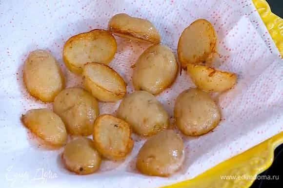 Обжаренный картофель выложить на бумажное полотенце, чтобы удалить излишки жира, и посолить.