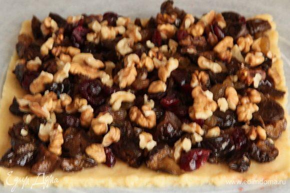 Раскатываем 2-й корж, смазываем его вареньем, выкладываем чернослив, сверху изюм и вишню, а потом орехи.