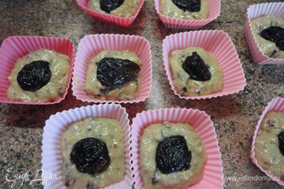 Соединить жидкие и сухие ингредиенты. В формочки (у меня поучилось 14 штук) выложить по 1 ст. л. теста. Выложить в каждую формочку по половинке или целому черносливу, сверху – оставшееся тесто.