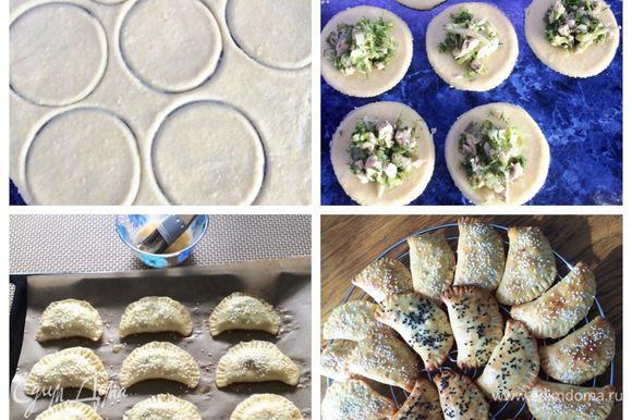 Охлажденное тесто раскатываем толщиной 3-5 мм. Вырезаем круги диаметром 8-10 см. Выкладываем ложкой в центр круга начинку и склеиваем пирожок, я еще вилочкой прошлась по краям. Выкладываем пирожки на противень, застеленный пекарской бумагой. Смазываем взбитым яйцом и посыпаем кунжутом (по желанию). Выпекаем в разогретой до 180°С духовке минут 30 до золотистого цвета (следим за духовкой).