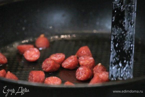 Отдельно обжарить нарезанную колбасу чоризо.