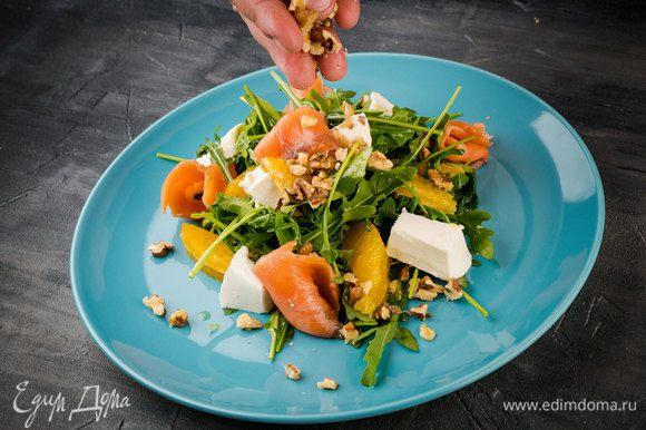 Все оставшиеся ингредиенты выложите на руколу, сбрызните лимоном и добавьте масла. И последний штрих — посыпьте раздробленными грецкими орехами.