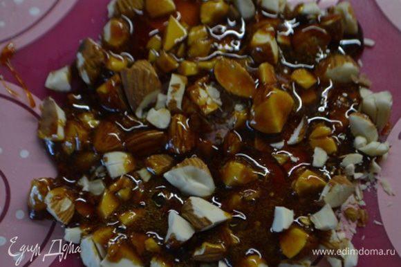 В сотейник всыпать сахар и нагреть до карамельного цвета (так как мы делали для желейных шариков), растопленный сахар вылить на орехи, остудить.