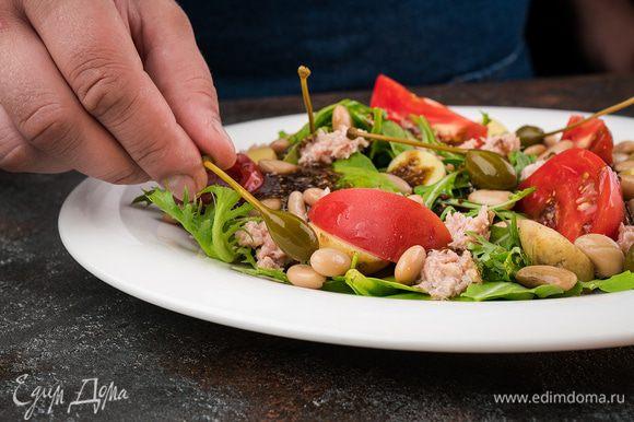 Полейте салат заправкой и украсьте каперсами.