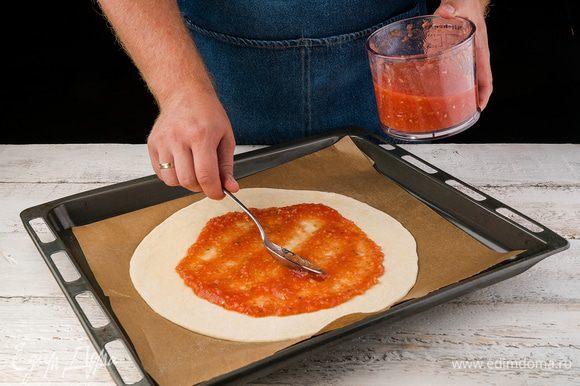 Когда тесто готово, раскатываем его тонким слоем и кладем на противень, покрытый бумагой для выпечки (бумагу для выпечки слегка смазываем оливковым маслом). Смазываем тесто слоем соуса.