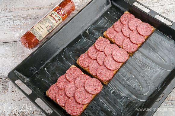 Выложить колбасу и засыпать сыром.