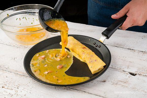 В тяжелой сковороде разогреть 1 ст. ложку оливкового масла и тонким слоем влить половину яичной смеси. Как только яичный корж схватится, немного завернуть один его край наверх, сдвинуть омлет на освободившееся место и половником влить еще немного яичной массы.