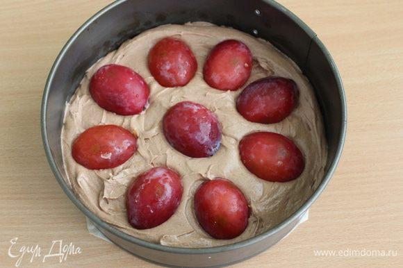Вылить тесто в смазанную форму диаметром 20 см, сверху выложить половинки слив срезом вниз.