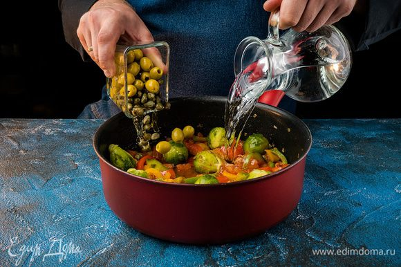Влить 3/4 литра воды и брюссельскую капусту. Добавить зеленые маслины и каперсы. Тушить 10 мин.