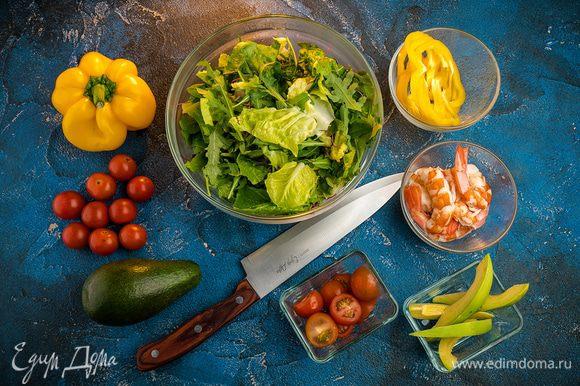 Салат порвать руками большими кусочками, добавить руколу. Перец нарезать кружочками, помидоры нарезать кружочками и пополам, авокадо натереть на терке или нарезать мелкой соломкой.