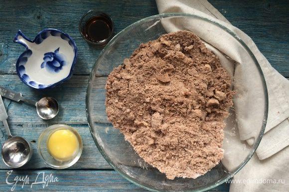 Добавьте сливочное масло, порезанное на кубики, щепотку соли и перемешайте до получения крошки. Введите желток, ванильный экстракт и 2 ст. л. холодной воды.