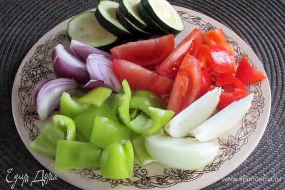 Подготовьте овощи для запекания. У перцев удалите семечки, а мякоть нарежьте на прямоугольные кусочки примерно 2х3 см. Помидоры нарежьте крупными дольками. Лук (тут половинка обычного репчатого и половинка сладкого фиолетового) разрежьте на 6 — 8 частей. Молодой кабачок или цукини — тонкими кружочками или ломтиками.