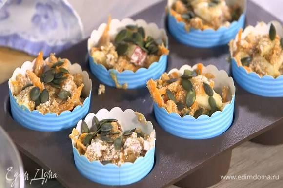 В формы для маффинов поместить бумажные вкладыши, разложить тесто, посыпать тыквенными семечками и оставшимся сахаром.