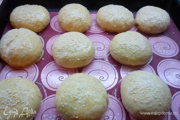 Булочки укладываем на слегка смазанный маслом противень (у меня силиконовый коврик) швом вниз. Оставляем булочки для расстойки на 30 — 40 минут, они должны увеличиться вдвое. По истечении этого времени смазываем булочки взбитым яйцом и посыпаем кунжутом.