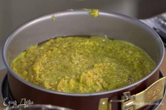 Разъемную форму для выпечки смазать растительным маслом, выложить тесто и разровнять его.