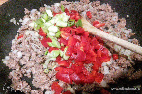 Добавить нарезанный мелким кубиком перец и кружочком зеленый лук (небольшое количество лука оставьте для подачи), обжарить вместе в течение нескольких минут.