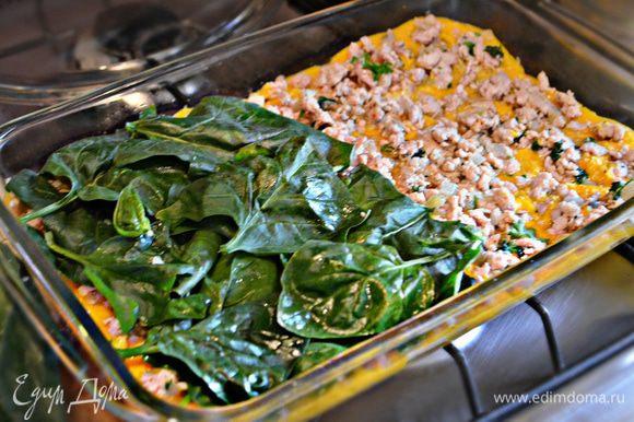 Налейте еще 2 стакана соуса и выложите половину обжаренного фарша. Следующим слоем положите половину шпината, сбрызните оливковым маслом. Посыпьте 1/4 сыра. Выложите еще 4 листа лазаньи и повторите слои.