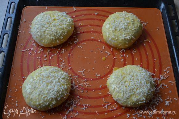 Выложить их на противень, застеленный пекарской бумагой, (или на силиконовый коврик). Смазать булочки яйцом и обильно посыпать натертым на мелкой терке пармезаном.