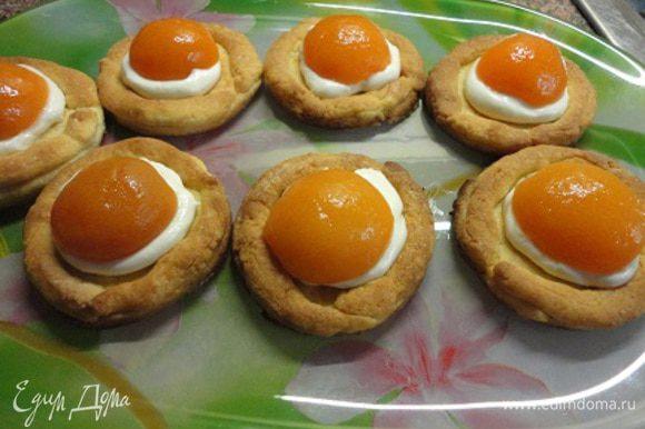 В середину каждого печенья выложить по чайной ложечке крема, сверху половинку абрикоса,