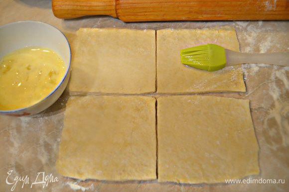 После охлаждения снова месите тесто еще несколько минут и оставьте его еще на полчаса, прежде чем раскатать в тонкий пласт. После нарежьте пласт на квадраты со стороной 10 см и смажьте поверхность взбитым яйцом.