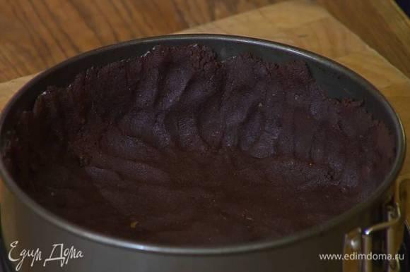 Разъемную форму для выпечки смазать оставшимся сливочным маслом и равномерно распределить тесто по дну и бортам. Часто наколоть тесто вилкой и отправить в разогретую духовку на 15 минут.