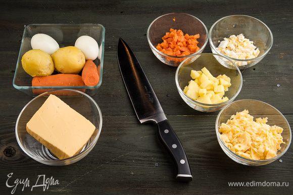 Картофель, морковь и яйца отварить и нарезать кубиками. Сыр натереть на мелкой терке.