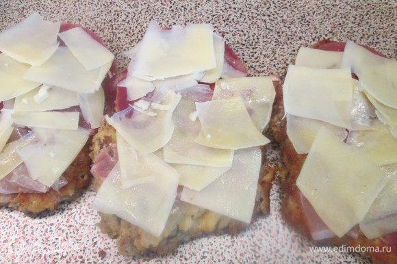 Отбивные перекладываем со сковороды на бумажное полотенце. Кладем на них кусочки копченой ветчины Прошутто, сверху кусочки пармезана и отправляем в форме для запекания в духовку. На дно вливаем бульон, который лишь смачивает дно.