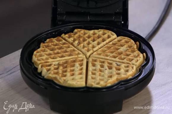 Разогреть вафельницу, смазать ее оливковым маслом и испечь вафли.