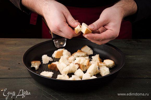 Хлеб нарезать кубиками и подсушить в духовке. С ананаса слить жидкость. Листья салата порвать. Сыр натереть на крупной терке.
