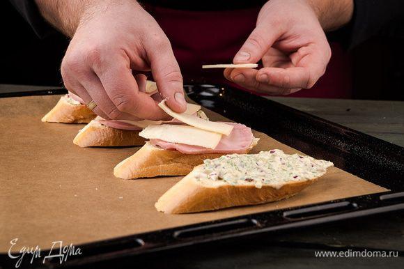 На каждый кусочек багета выложить топпинг, сверху накрыть его ветчиной и слайсом сыра. Поставить в духовку на 5 минут при 180°С.