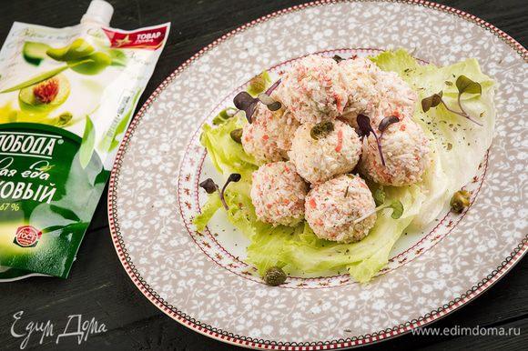 Выложить шарики на листья салата, украсить оливками и подавать к столу.