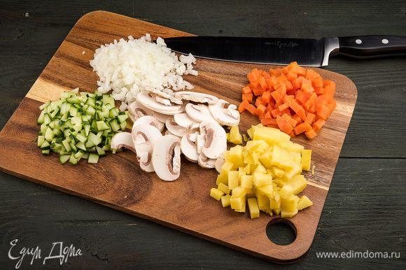 Отвариваем картофель и морковь. Нарезаем кубиками картофель, морковь, лук, огурцы и грибы. Измельчаем петрушку.